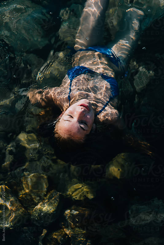 Young girl laying on her back, floating on the water by Boris Jovanovic for Stocksy United
