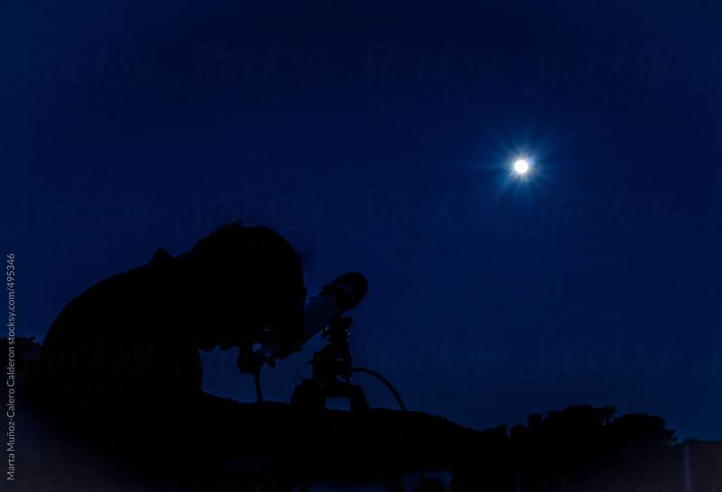 Man looking at the moon through a telescope by Marta Muñoz-Calero Calderon for Stocksy United