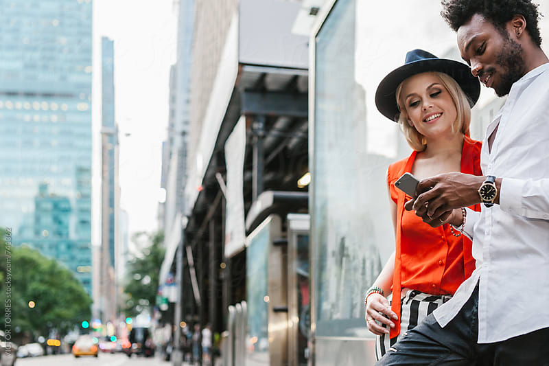 Multi-ethnic Couple Using a Mobile Phone in the Streets of Manhattan, New York by Victor Torres for Stocksy United