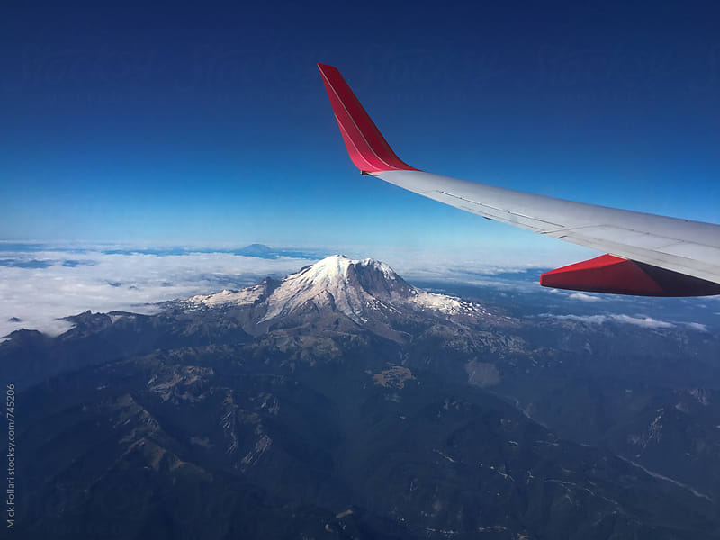 Snow-capped mountain and airplane wing by Mick Follari for Stocksy United