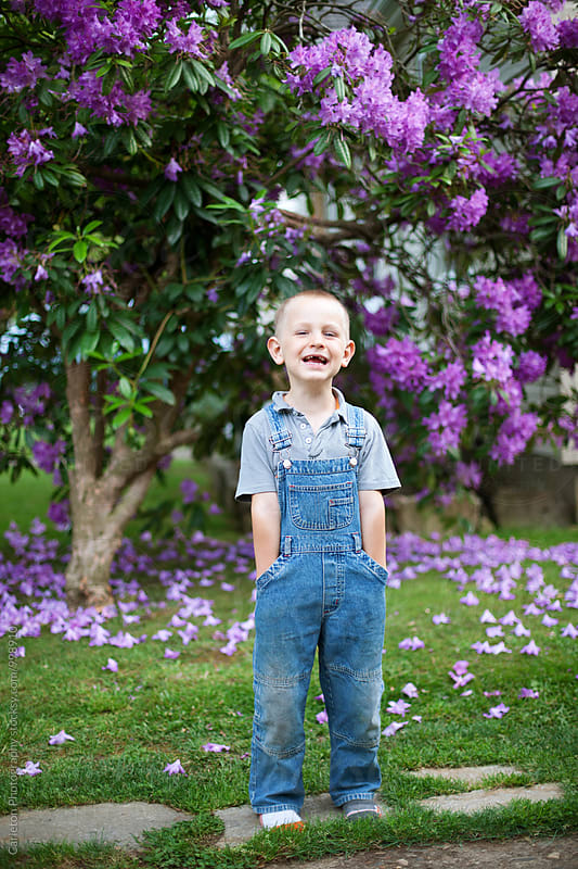 Five year old boy in overalls laughing by Carleton Photography for Stocksy United