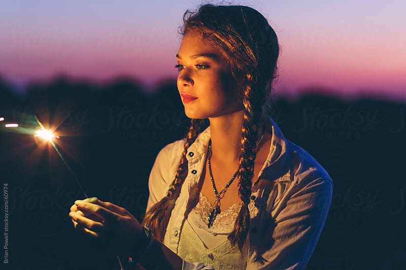young woman lit by sparkler by Brian Powell for Stocksy United