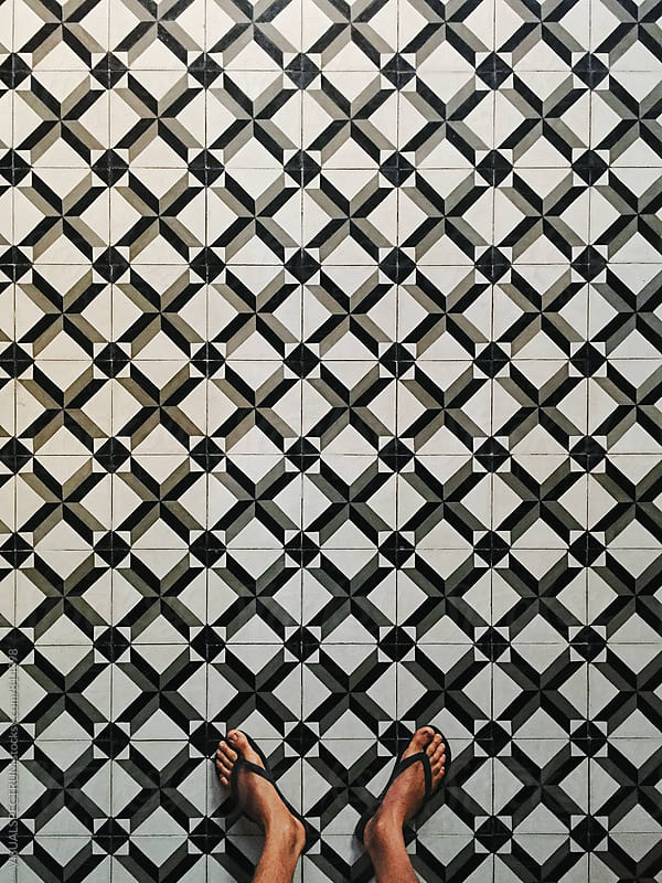 Man in Flip-Flops Standing on Retro Tiles by Julien L. Balmer for Stocksy United