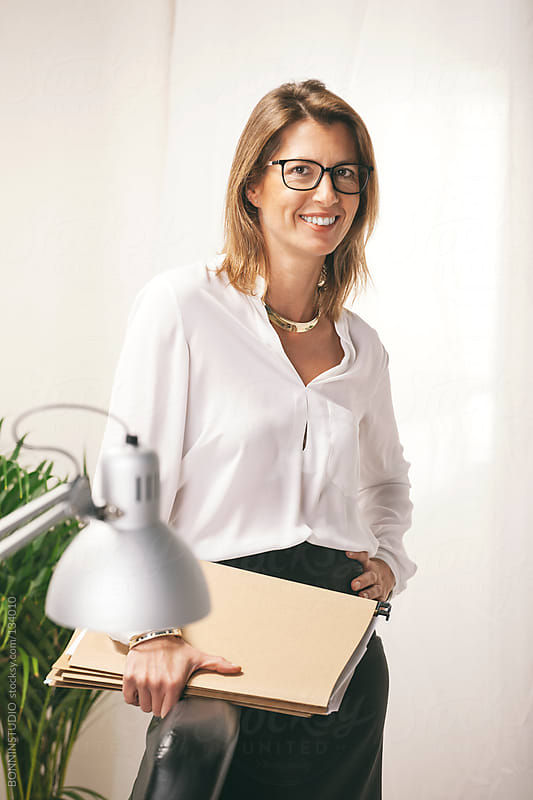 Mature business woman with a documents at office, Elegant woman smiling. by BONNINSTUDIO for Stocksy United