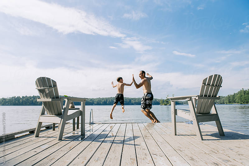 Boy and dad high five as they leap off a dock together by Cara Dolan for Stocksy United
