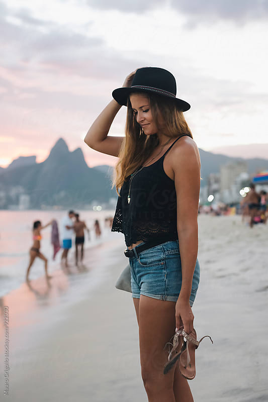 Rio de Janeiro. Brazil. Woman walking on the beach at sunset by Mauro Grigollo for Stocksy United
