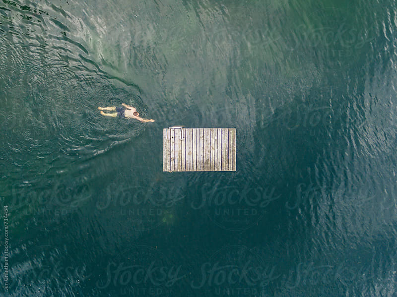 Young man swimming towards an old raft by Jen Grantham for Stocksy United