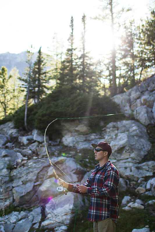 Man fly fishing at an alpine lake by Hannah Dewey for Stocksy United