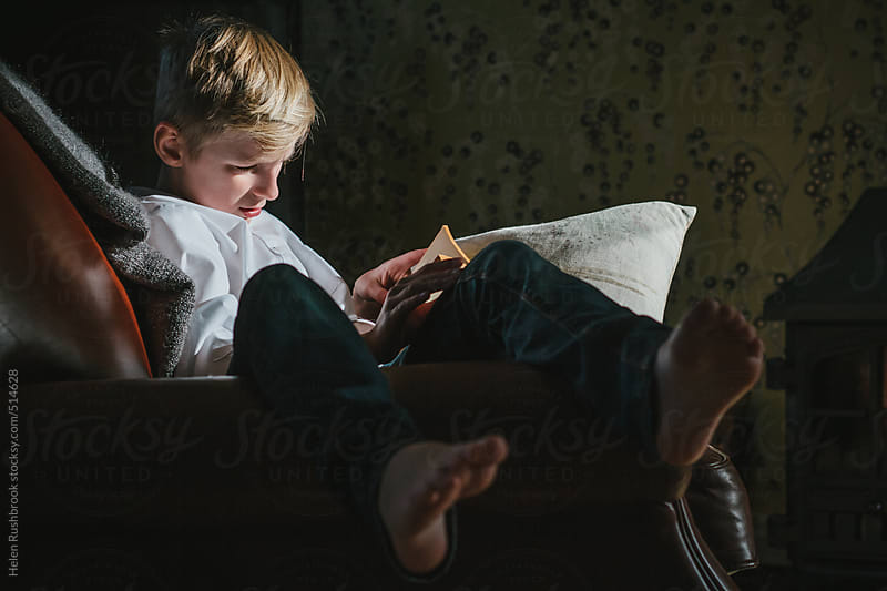 A boy in an armchair, reading. by Helen Rushbrook for Stocksy United