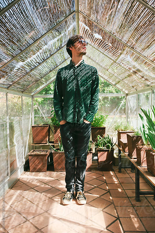Young man with sunglasses standing on a greenhouse. by BONNINSTUDIO for Stocksy United