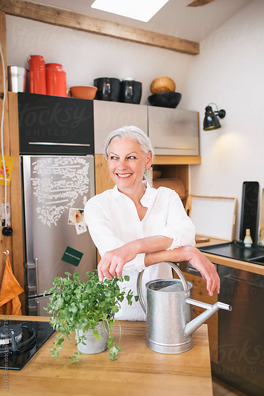 Senior woman with a cilantro plant and watering can in her kitchen. by Lilly Bloom for Stocksy United