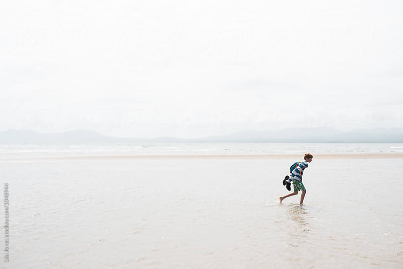 boy running on the beach by Léa Jones for Stocksy United