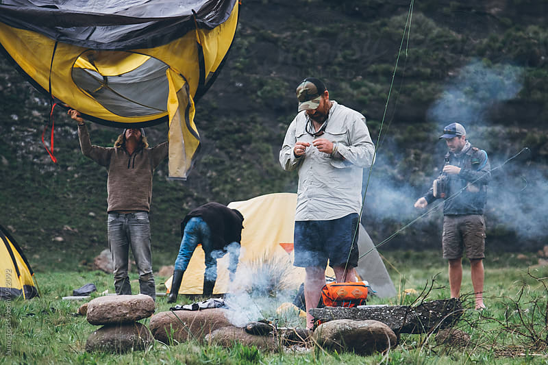 hikers and fly fishermen packing up a camp in the mountains by Micky Wiswedel for Stocksy United