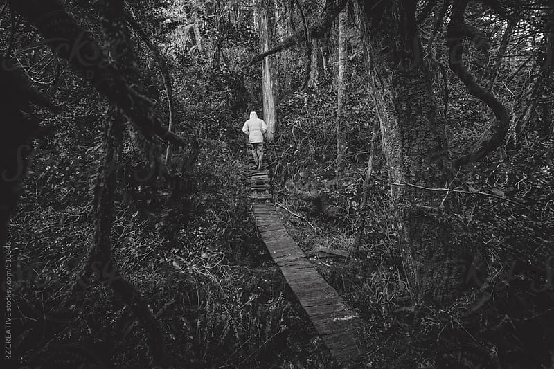 A figure walking through a forest. by RZ CREATIVE for Stocksy United
