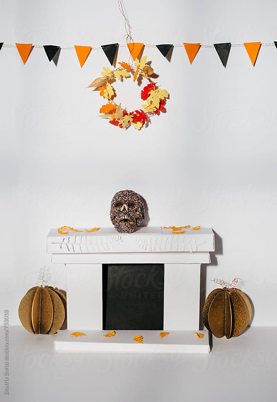 Skull decorated with pearls on the fireplace in a paper craft room decorated for halloween by Beatrix Boros for Stocksy United