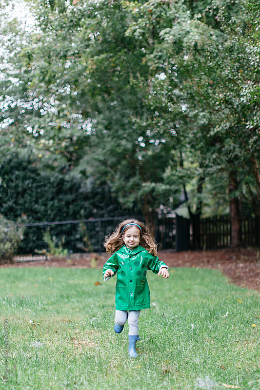 Cute young girl running in a raincoat outside by Jakob for Stocksy United