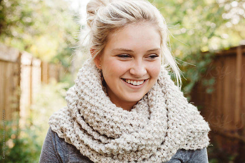 Laughing young woman wearing cream knit scarf by Carey Shaw for Stocksy United