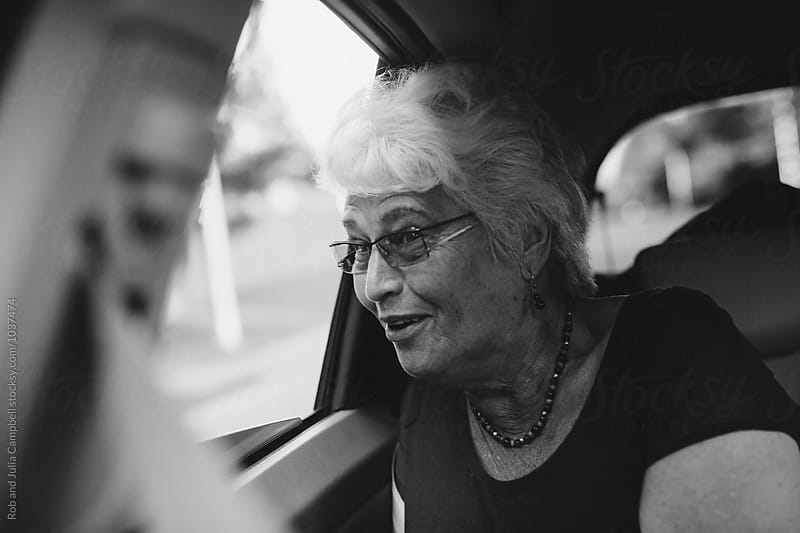 Happy, excited caucasian senior woman leaning out moving car window by Rob and Julia Campbell for Stocksy United