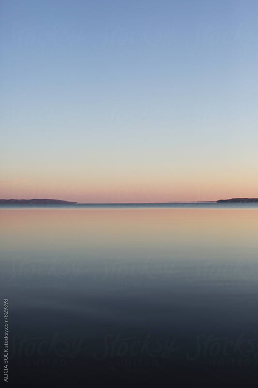 Sunrise Reflected Over A Calm Lake On A Clear Morning by ALICIA BOCK for Stocksy United