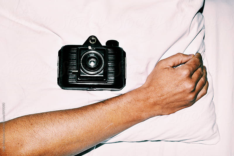 old film camera in bed by juan moyano for Stocksy United