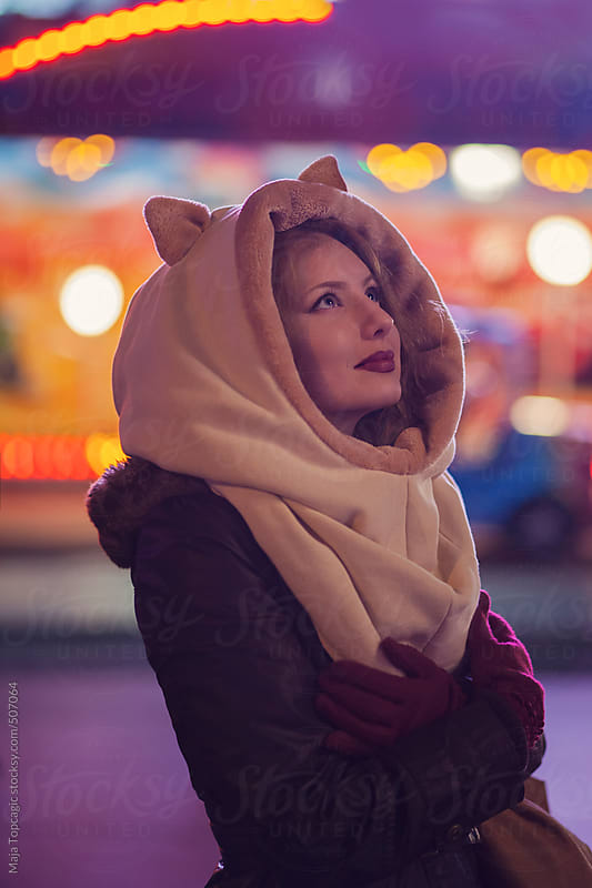 Young beautiful woman wit a beige cat hat in the city at night by Maja Topcagic for Stocksy United