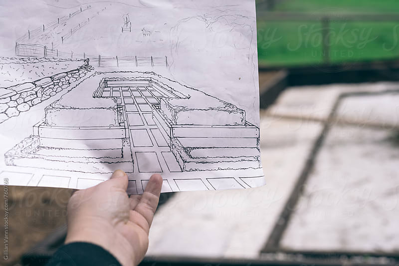 hand holding some home drawn plans for an outdoor vegetable garden and courtyard by Gillian Vann for Stocksy United