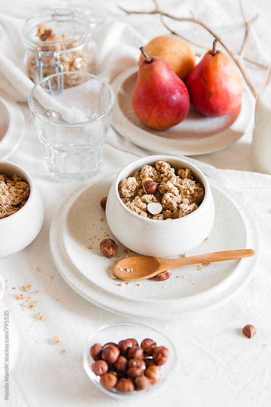 Granola in white bowls and fruit by Nataša Mandić for Stocksy United