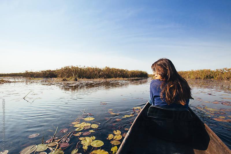 Woman on a mokoro canoe in the Okavango swamp by Micky Wiswedel for Stocksy United