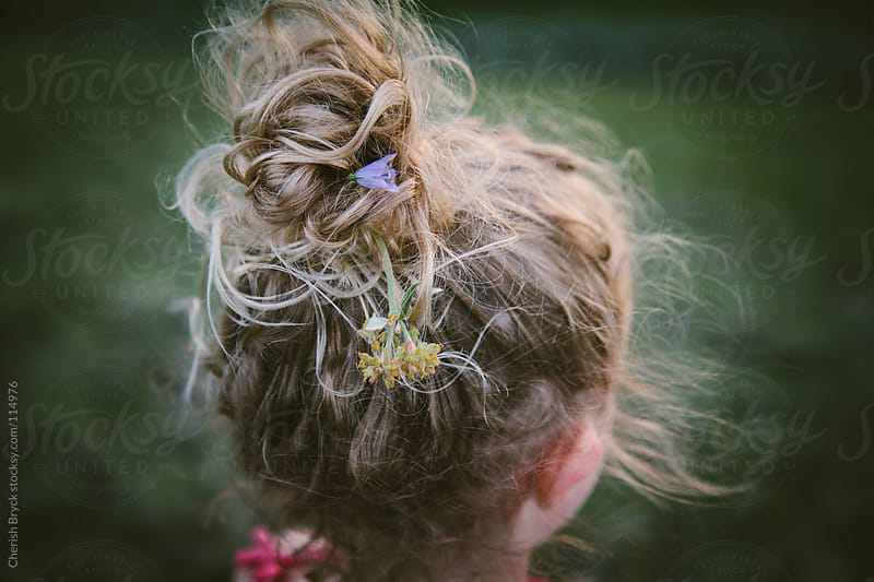 Little girl's hair is full of wild flowers. by Cherish Bryck for Stocksy United