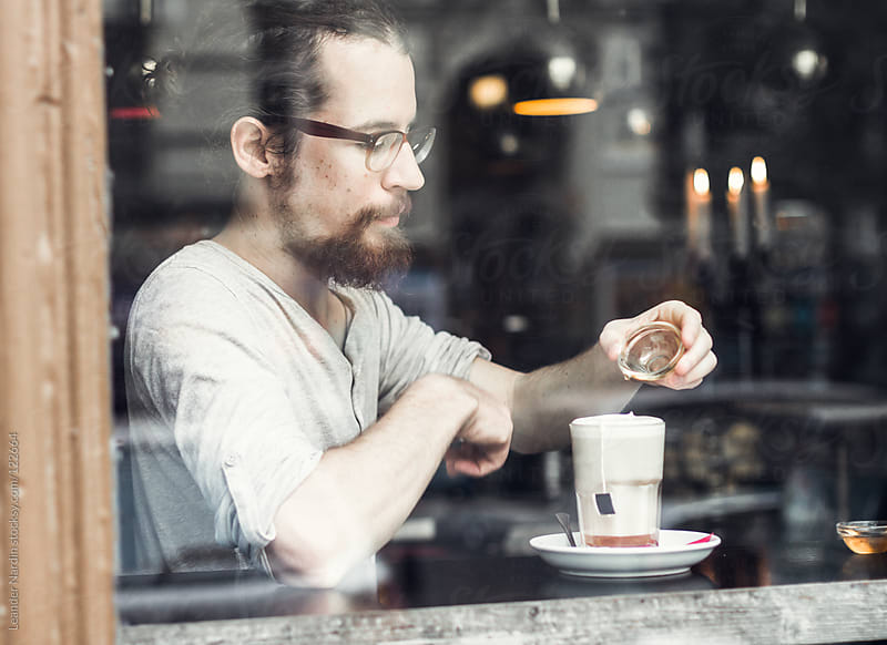young, bearded man sitting in a cafe and puts some honey into his tea  by Leander Nardin for Stocksy United