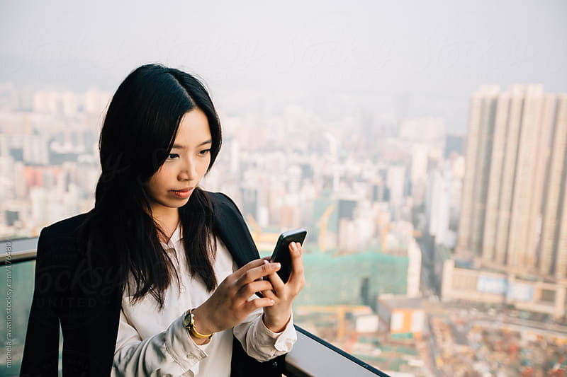 Asian businesswoman using her cellphone by michela ravasio for Stocksy United