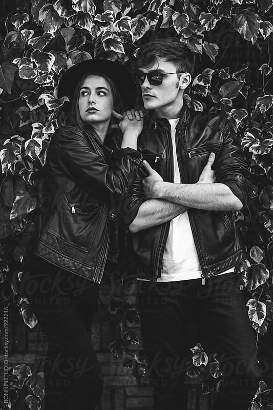 Portrait of alternative couple standing in front of an ivy wall. by BONNINSTUDIO for Stocksy United