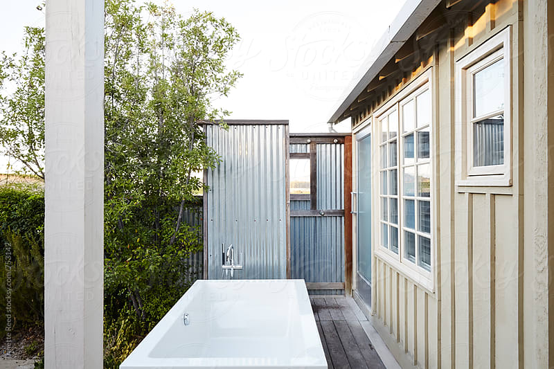 Outdoor bathroom with tub and shower on patio of cottage by Trinette Reed for Stocksy United