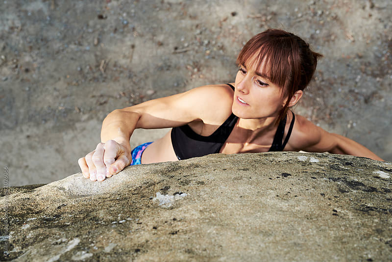 Sportswoman climbing the rock with hands by Guille Faingold for Stocksy United
