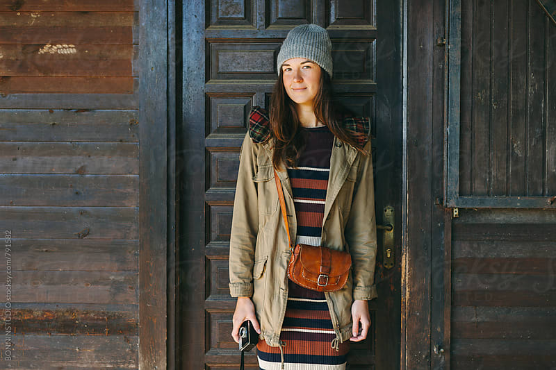 Hipster woman standing in front of a wooden cabin on the mountain. by BONNINSTUDIO for Stocksy United