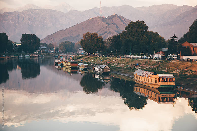 Houseboats lining the reflective Dal Lake, India, at dusk by Maresa Smith for Stocksy United