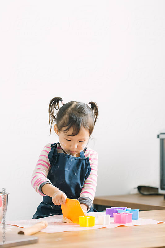 Toddler girl making cookies by Maa Hoo for Stocksy United