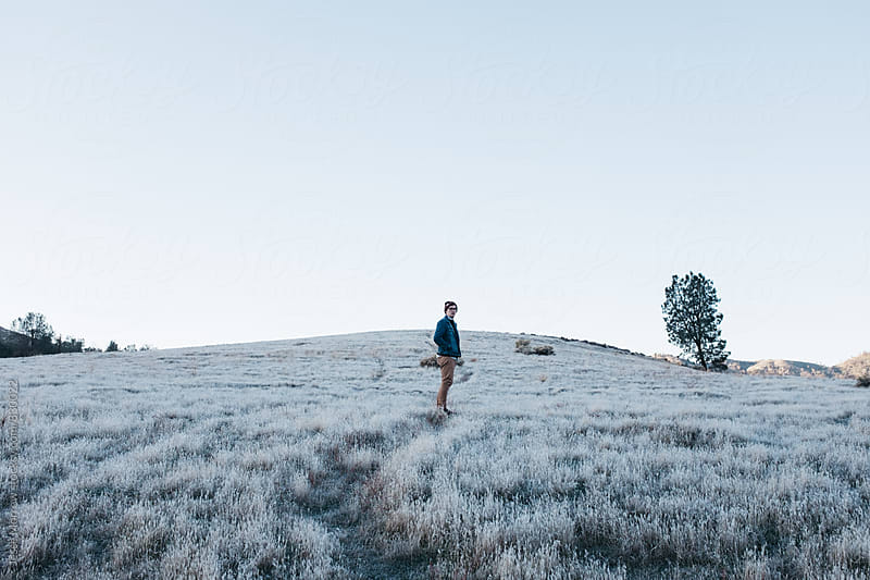 person walking through frosty field in cold morning outdoors by Jesse Morrow for Stocksy United