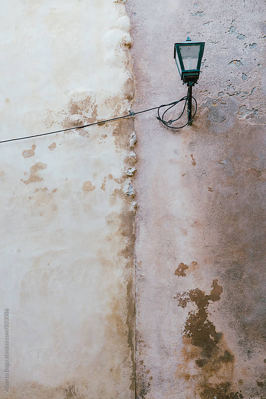 Old street lamp hanging on white dirty wall by Alberto Bogo for Stocksy United