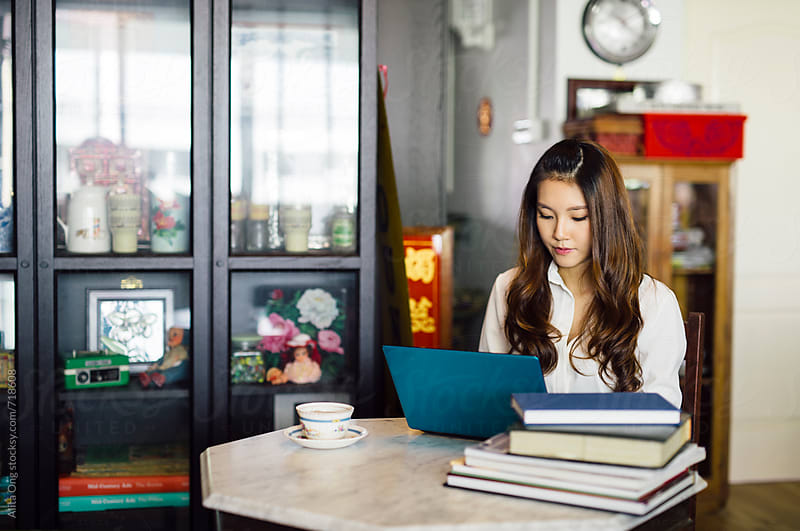 A young Asian woman at home, working on a laptop by Alita Ong for Stocksy United