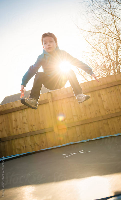 Boy jumping on a trampoline by Craig Holmes for Stocksy United
