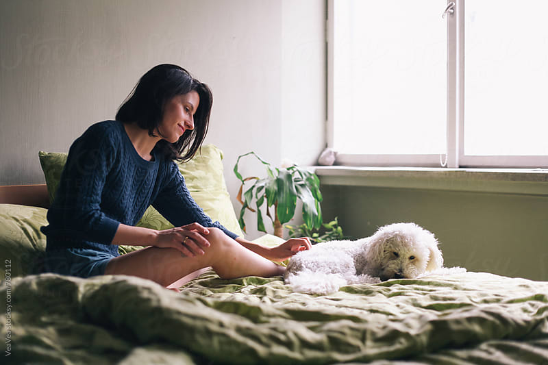Woman and her white poodle sitting in the bed  by Marija Mandic for Stocksy United