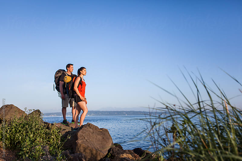 Hiking couple standing on the rock enjoying the scenery by Suprijono Suharjoto for Stocksy United