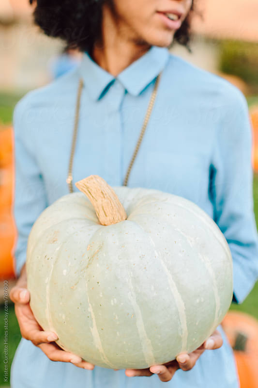 A woman holding a white pumpkin by Kristen Curette Hines for Stocksy United