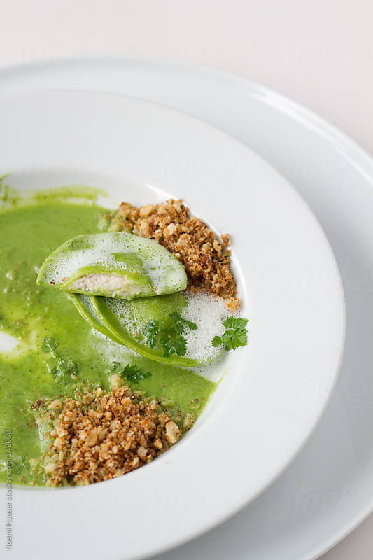 Halved green ravioli in sauce with herb and crumble by Noemi Hauser for Stocksy United
