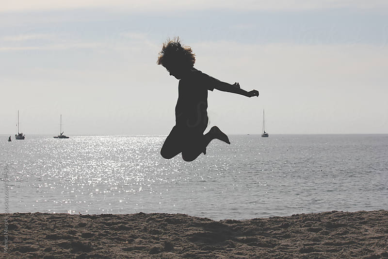 Silhouette of young boy jumping in the sand at the beach by Monica Murphy for Stocksy United