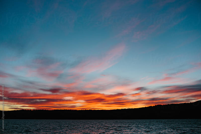 sunset over lake by Cameron Zegers for Stocksy United
