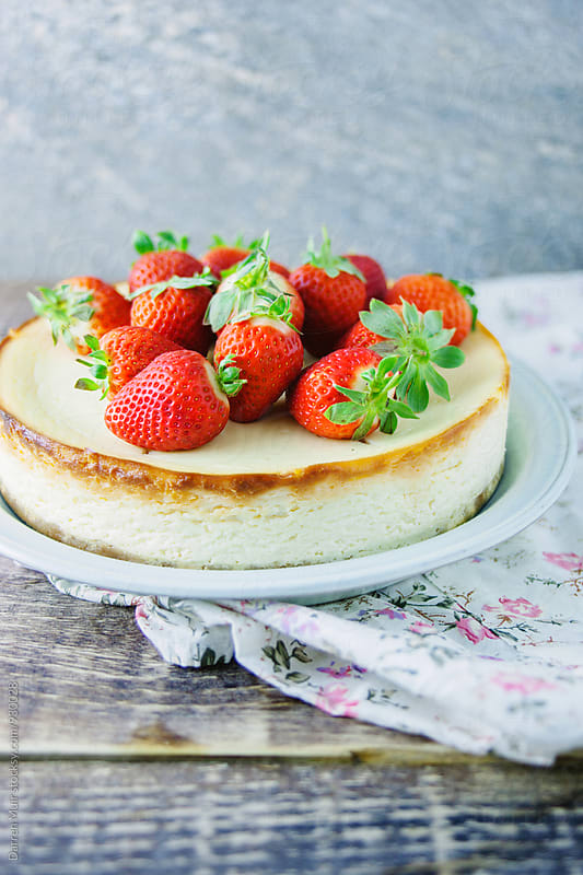 Vanilla cheesecake, topped with strawberries.  by Darren Muir for Stocksy United
