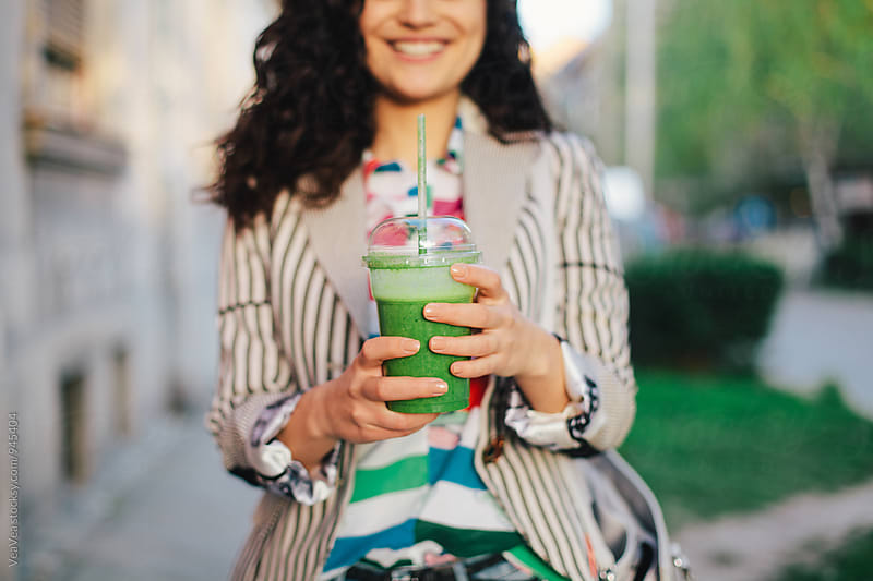 Woman holding green smoothie  by VeaVea for Stocksy United