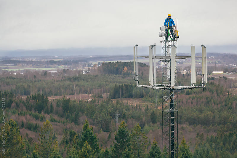 Working at heights, technician climbs up on a communications tower by Jelena Jojic Tomic for Stocksy United